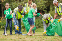 Volunteers wearing safety vests and gloves and using pickers gather litter and place it in green trash bags in a park